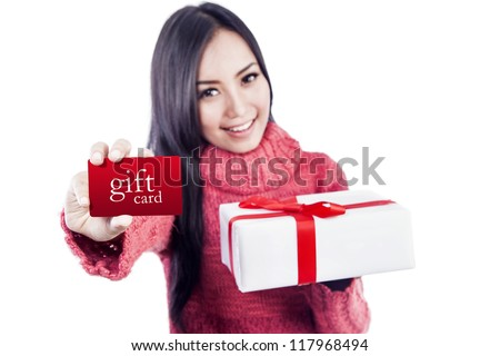Asian woman is showing a gift card while holding a present - stock photo