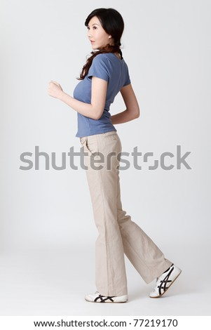 Asian woman jogging, full length portrait isolated on gray studio background.