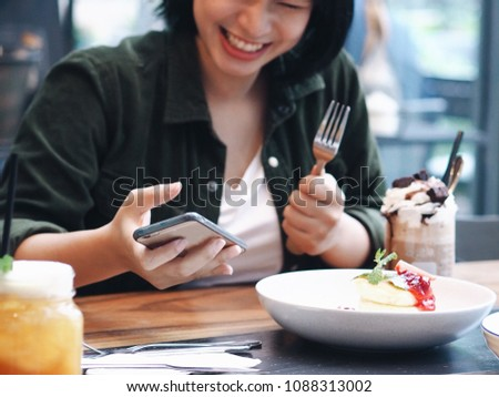 Asian woman joyful with food in restaurant,she eating delicious dessert dish and take a picture of food and herself.food blogger concept.