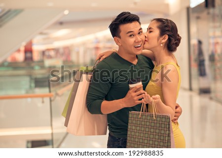Asian woman kissing her boyfriend in the store