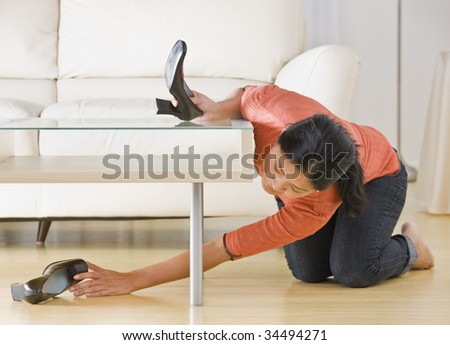 Asian woman kneeling on floor and reaching for shoe under coffee table. Horizontal.
