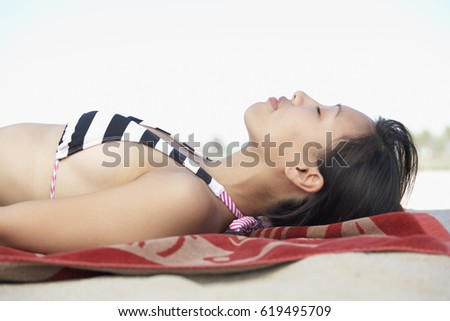 asian woman laying on blanket...