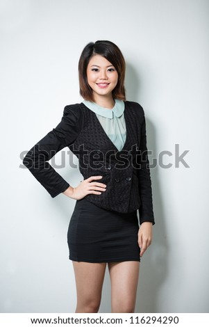Asian Woman leaning against white wall with her hand on hip.