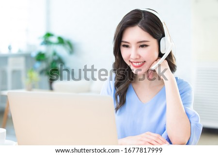 asian woman learning language during internet online courses and she search information via laptop computer at home