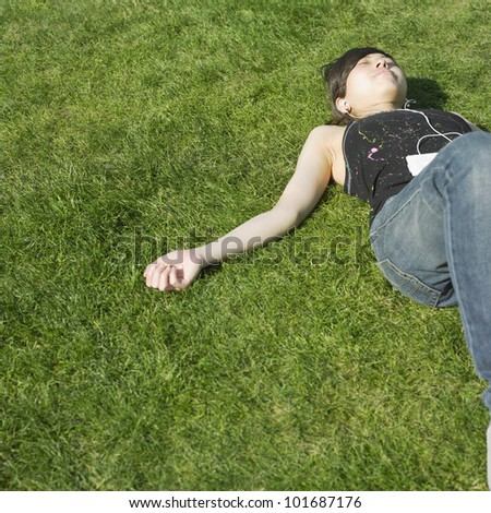 Asian woman listening to mp3 player in grass
