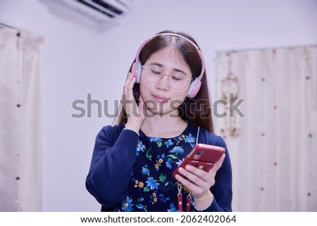 Asian woman listening to music with headphones with a smartphone in one hand