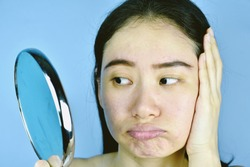 Asian woman looking at her facial problem in the mirror, Female feeling annoy about her reflection appearance show the aging skin signs, wrinkles, dark spot, pimple, acne scar, large pores, dull skin.