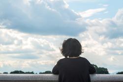 Asian woman looking at sky and lake