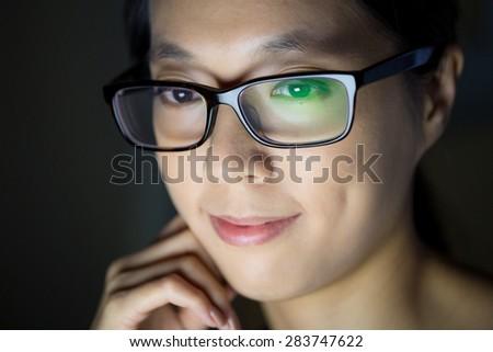 Asian woman looking at the screen at night