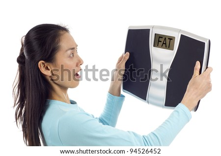 "Asian woman looking surprised at her weight, Digital scale displaying the word "" FAT""  isolated over white background"