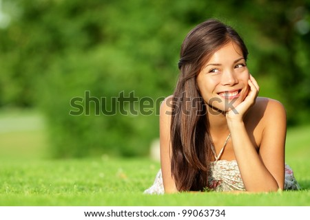 Asian woman lying in grass smiling happy looking at copy space. Beautiful girl in spring / summer relaxing and thinking. Mixed race Caucasian / Asian Chinese model outdoors.