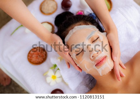 Asian Woman lying with a sheet mask on her face.Wellness body care and spa aromatherapy concept. #1120813151
