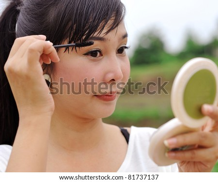 Asian woman making up her face