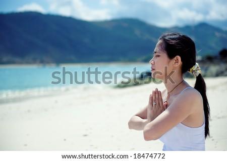 asian woman meditating on the beach