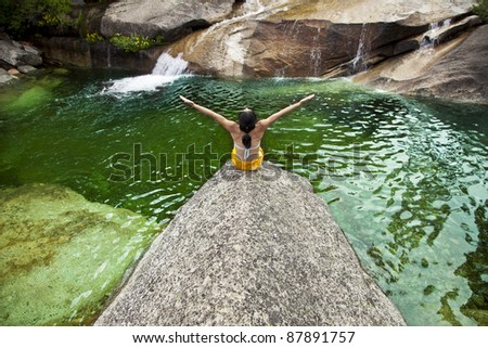 Asian woman meditating on the edge of a natural pool.