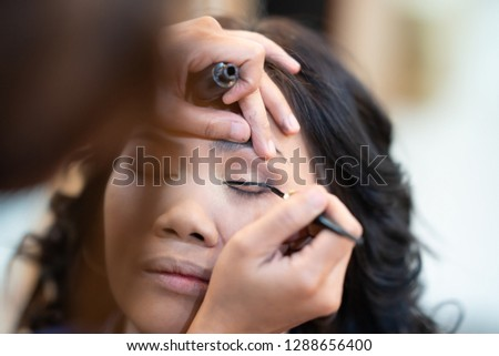 73f8e2d4741 Young beautiful woman applying make up. #1297844527 · Asian woman model false  eyelashes during make-up session. The make-up artist
