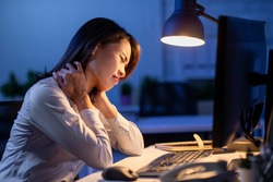 asian woman overtime work and feel shoulder pain in the office