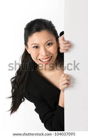 Asian woman peering around from behind a white wall.