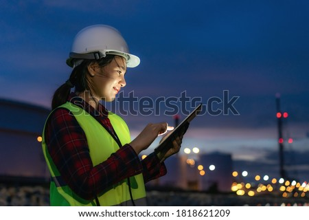 Asian woman petrochemical engineer working at night with digital tablet Inside oil and gas refinery plant industry factory at night for inspector safety quality control.