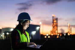 Asian woman petrochemical engineer working at night with laptop Inside oil and gas refinery plant industry factory at night for inspector safety quality control.