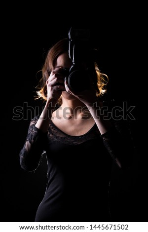 Asian Woman Photographer hold camera with external flash point to shoot subject, wear body suit. studio lighting black background isolated low key exposure, reporter journalist take photo celebrity