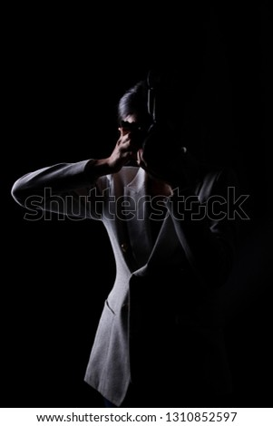 Asian Woman Photographer hold camera with external flash point to shoot subject, wear gray suit. studio lighting black background isolated low key exposure, reporter journalist take photo celebrity