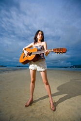 asian woman playing a guitar standing by the beach