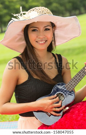 Asian woman playing ukulele in the park