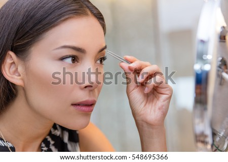 Asian woman plucking eyebrows with tweezers using eyebrow tweezer at home in bathroom makeup mirror. Closeup of a girl's face while she is removing her facial hairs. Eyebrows beauty care.