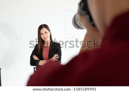 Asian woman posing posing in front of an Asian male photographer. In which she poses with her arms crossed With the backdrop being studio lights.