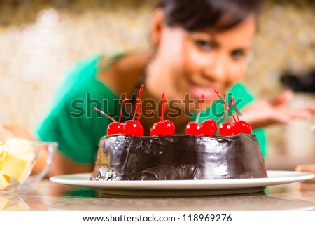 Asian woman presenting homemade chocolate cake with cherries she baked in her kitchen for dessert