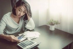 Asian woman press hand in head and other side hold a credit card. Feeling stress, unhappy, worry about the receipt or slip and the calculator in front for calculate payment or burden of over shopping