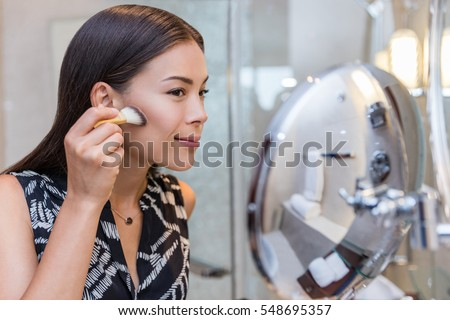 Asian woman putting makeup in home bathroom using a contour brush to apply bronzer powder under cheek bones, then blend it upwards onto cheeks. Morning routine in make-up mirror.