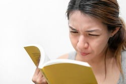 Asian woman reading book, has bad vision sight problems, selective focus, myopia and eyesight problem concept.