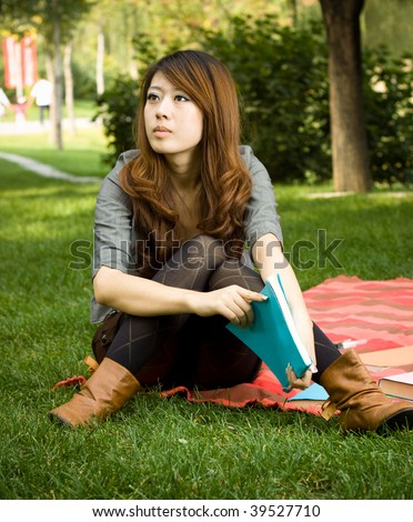 Asian woman reading book in a park