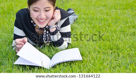 Asian woman reading notebook on the grass