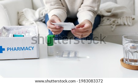 Asian woman receive medication package box free first aid kit from pharmacy hospital delivery service at home in telehealth telemedicine online concept. Check medicine box capsule pack from drugstore. Сток-фото ©