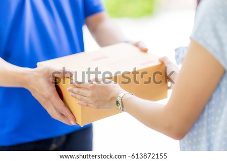 Asian woman receiving a package at home from a delivery guy ストックフォト ©