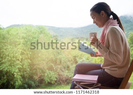 Asian Woman relax while holds a book and a cup of coffee in the morning. she was relaxed and enjoying the nature around. relaxing  on green mountain background,  #1171462318