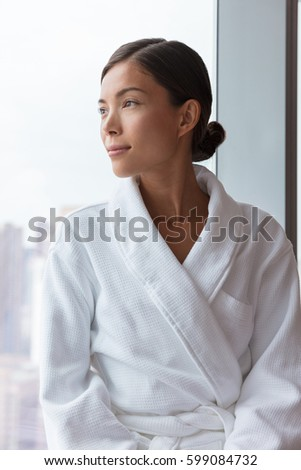 Asian woman relaxing at luxury hotel spa wearing bathrobe looking at window portrait. Pampering travel lifestyle at resort. #599084732