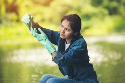 Asian woman researcher black hair in blue jean volunteer charity working checking controlling the quality of water environment with glass tube at green forest near river at ratchaburi thailand.