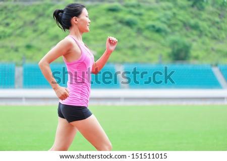 asian woman runner running in sports ground outdoor