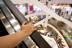 Asian woman's hand holding the escalator handrail.