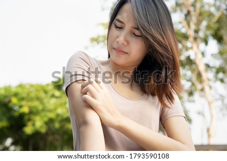 Asian woman scratching her arm; concept of dry skin, allergic skin inflammation, body care, fungus infection, eczema, dermatitis, rash, mosquito or insect bite