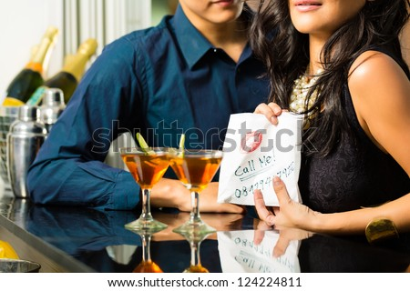 Asian woman seduces the man in restaurant and gives him her number on a napkin - stock photo