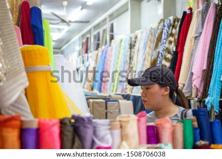 Asian woman selecting many kinds of cloth in fabric shop