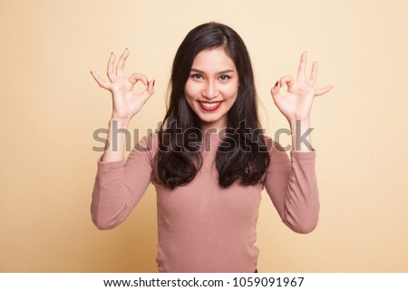 Asian woman show double OK hand sign  and smile on beige background #1059091967