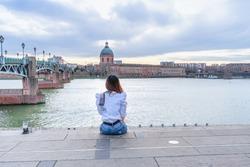 Asian woman sitting Garonne river and Dome de la Grave in Toulouse, France