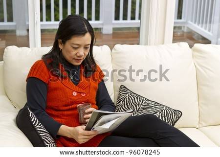 Asian woman sitting on white leather couch with coffee mug and magazine in hands