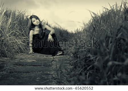 asian woman sitting outdoor with black dress in the meadow
